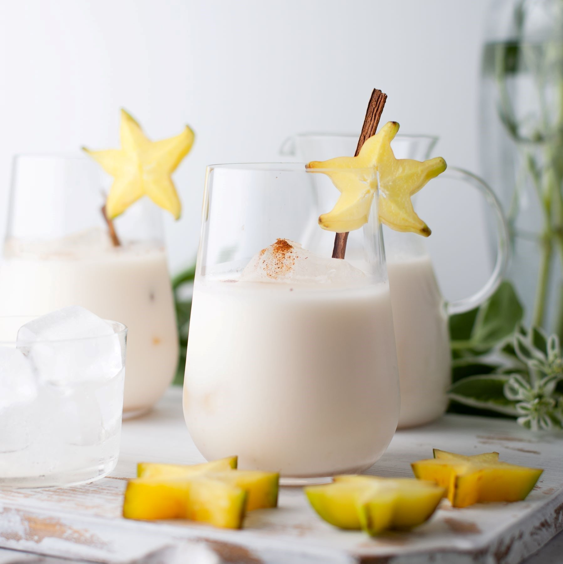 Glasses filled with creamy homemade horchata garnished with a cinnamon stick and starfruit.