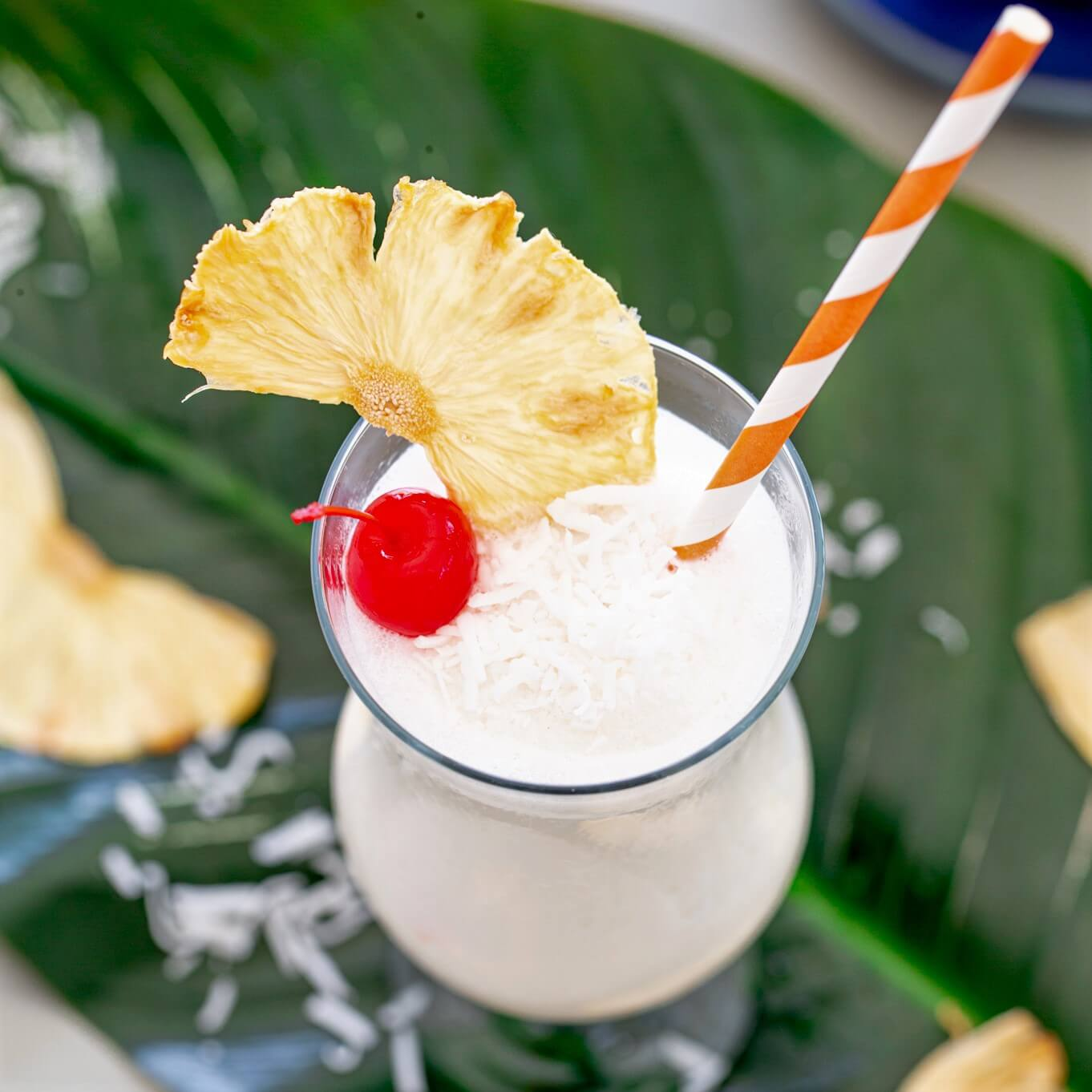 Top view of a Pina Colada garnished with a wedge of pineapple, a cherry, and shredded coconut.