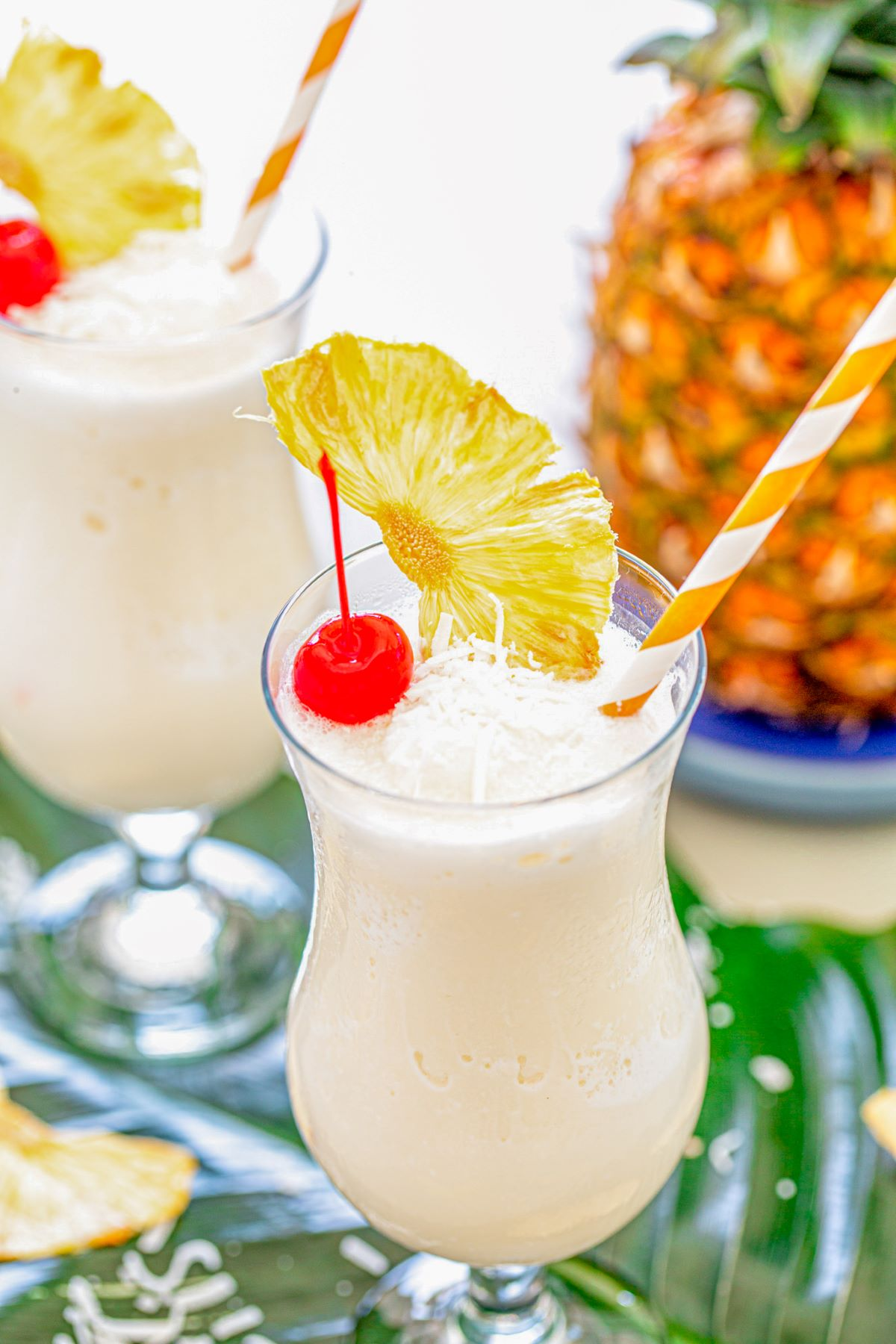 Two pina coladas garnished with a red cherry, dried pineapple wedge, and shredded coconut.