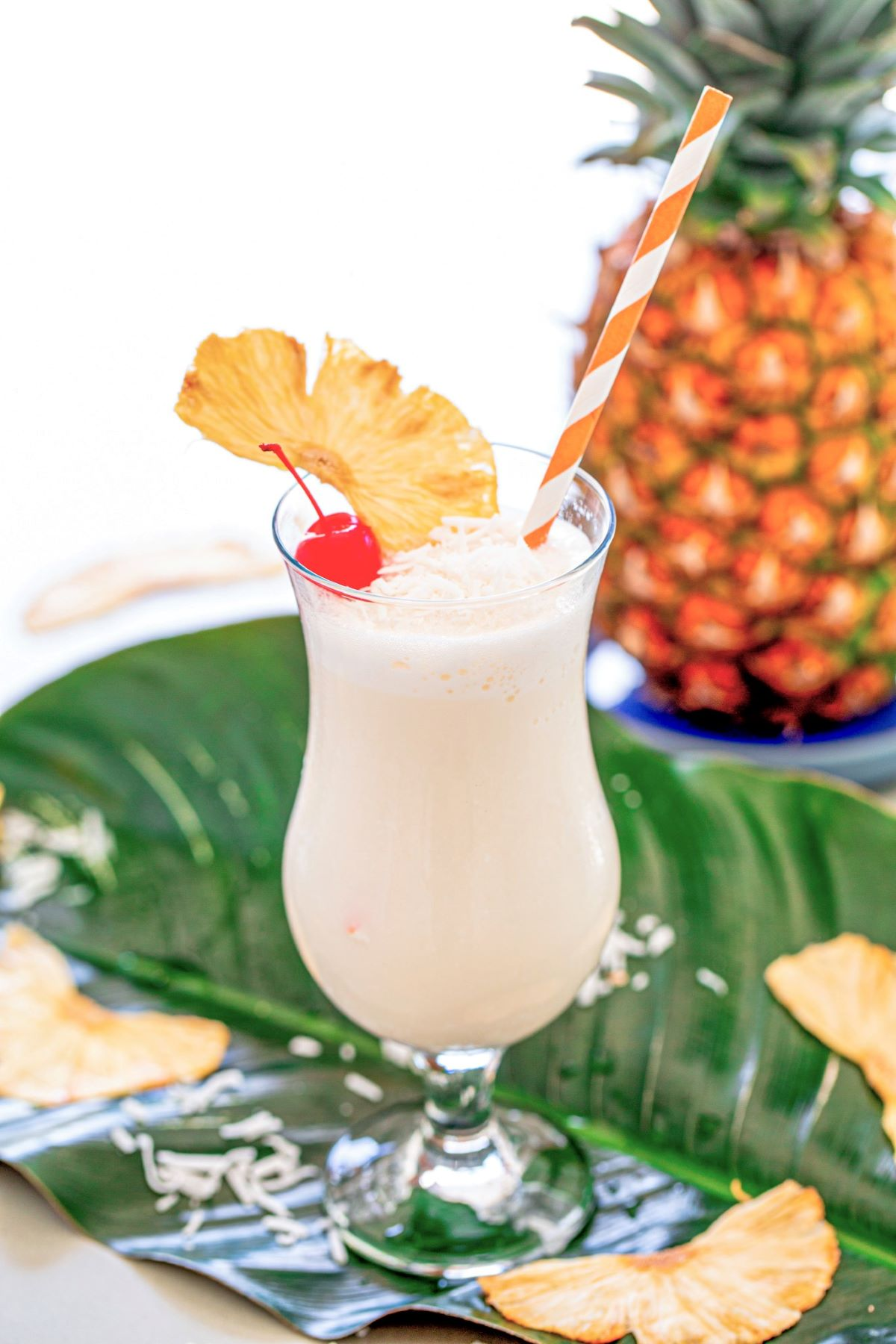 A pina colada garnished with a red cherry, dried pineapple wedge, and shredded coconut.