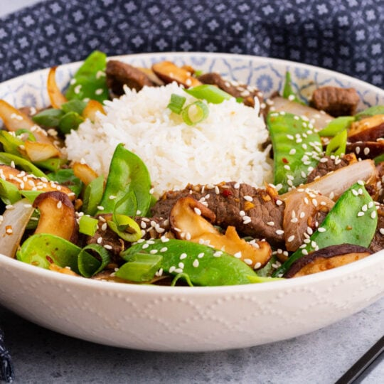 A bowl filled with beef stir fry and snow peas, white rice, shiitake mushrooms topped with sesame seeds and sliced green onions.