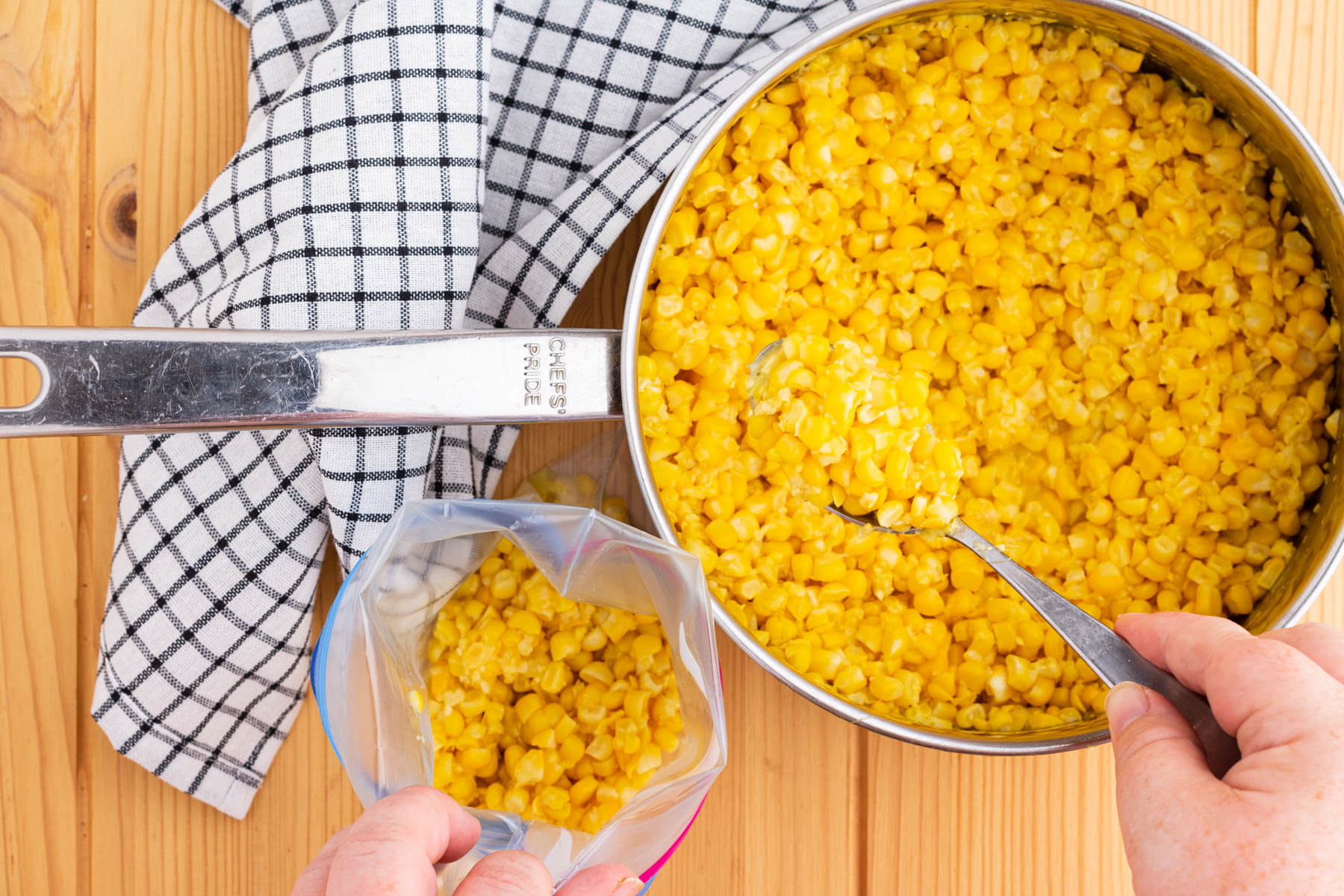 Filling up a freezer bag with corn from a saucepan filled with yellow corn.