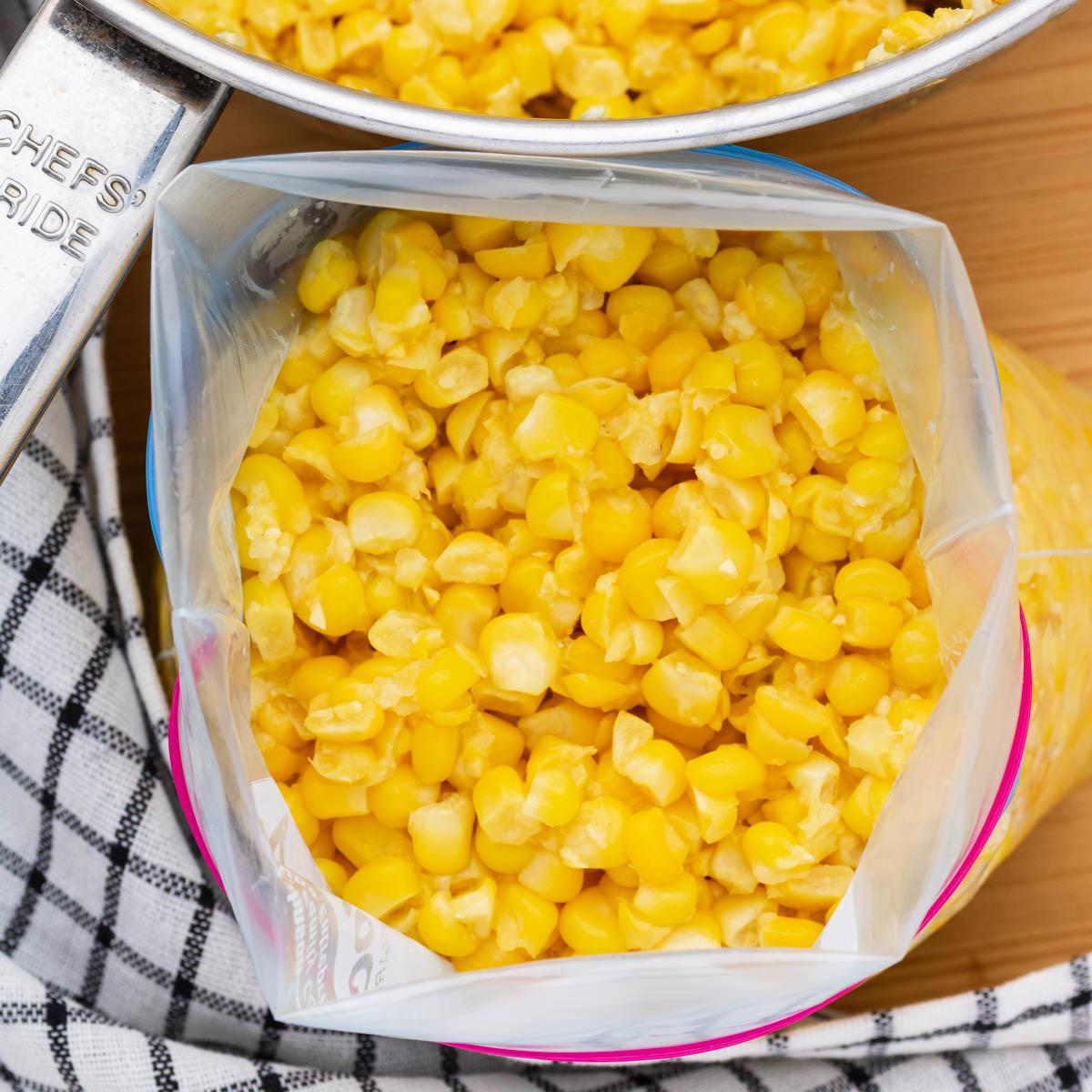 A freezer bag full of bright yellow corn kernels beside a saucepan of corn.