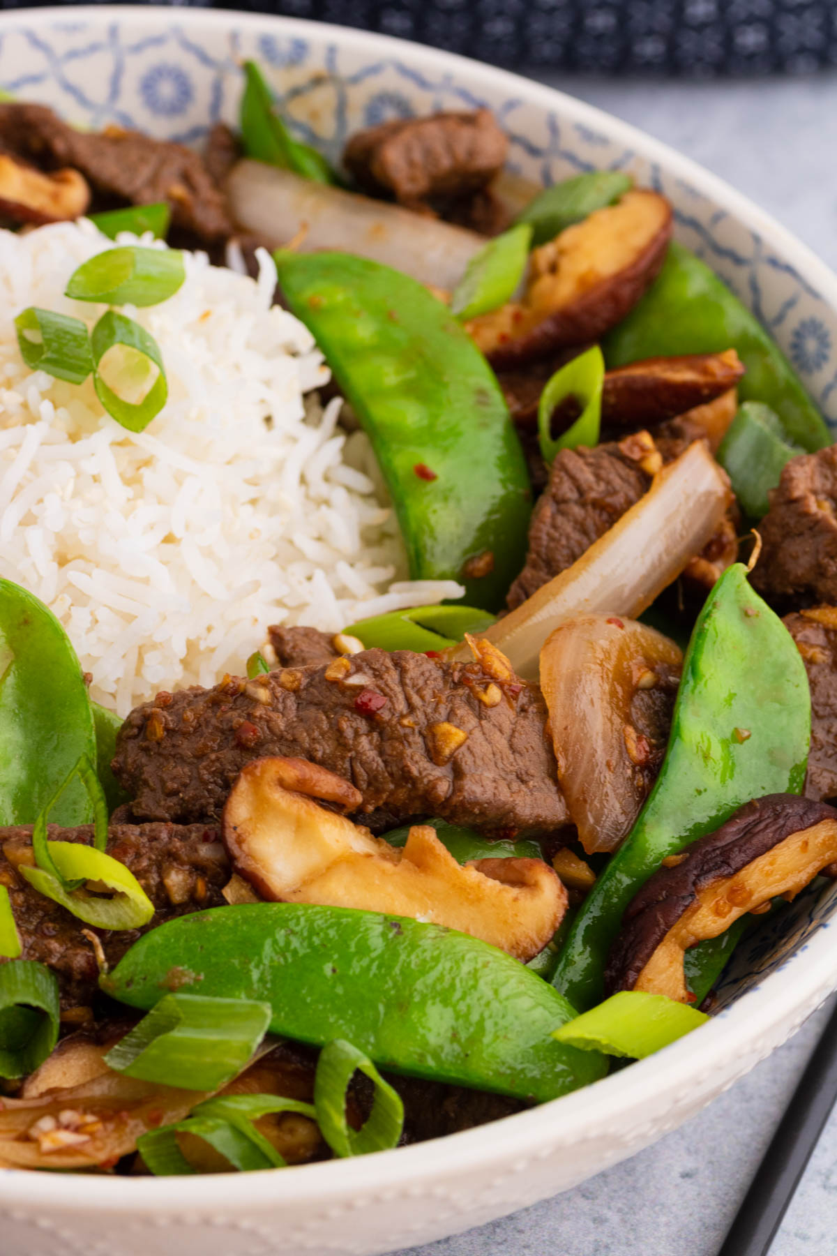 A bowl filled with beef stir fry and snow peas, white rice, shiitake mushrooms.