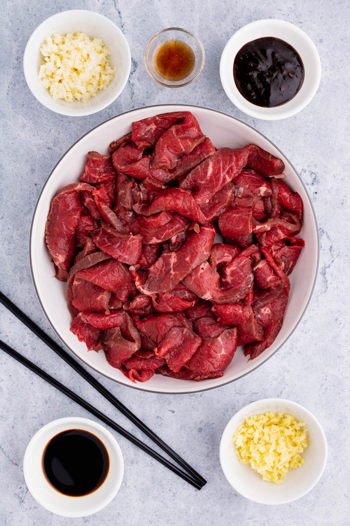 Strips of beef in a bowl surrounded by marinade ingredients.