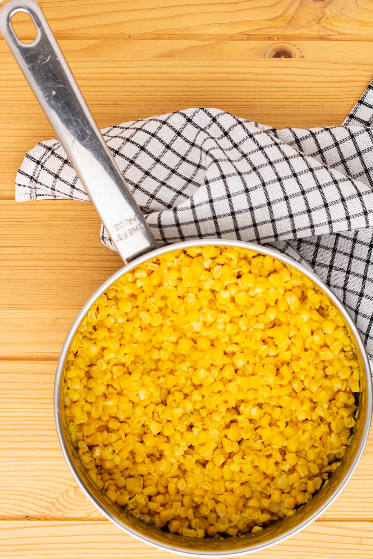 A saucepan filled with yellow corn kernels.