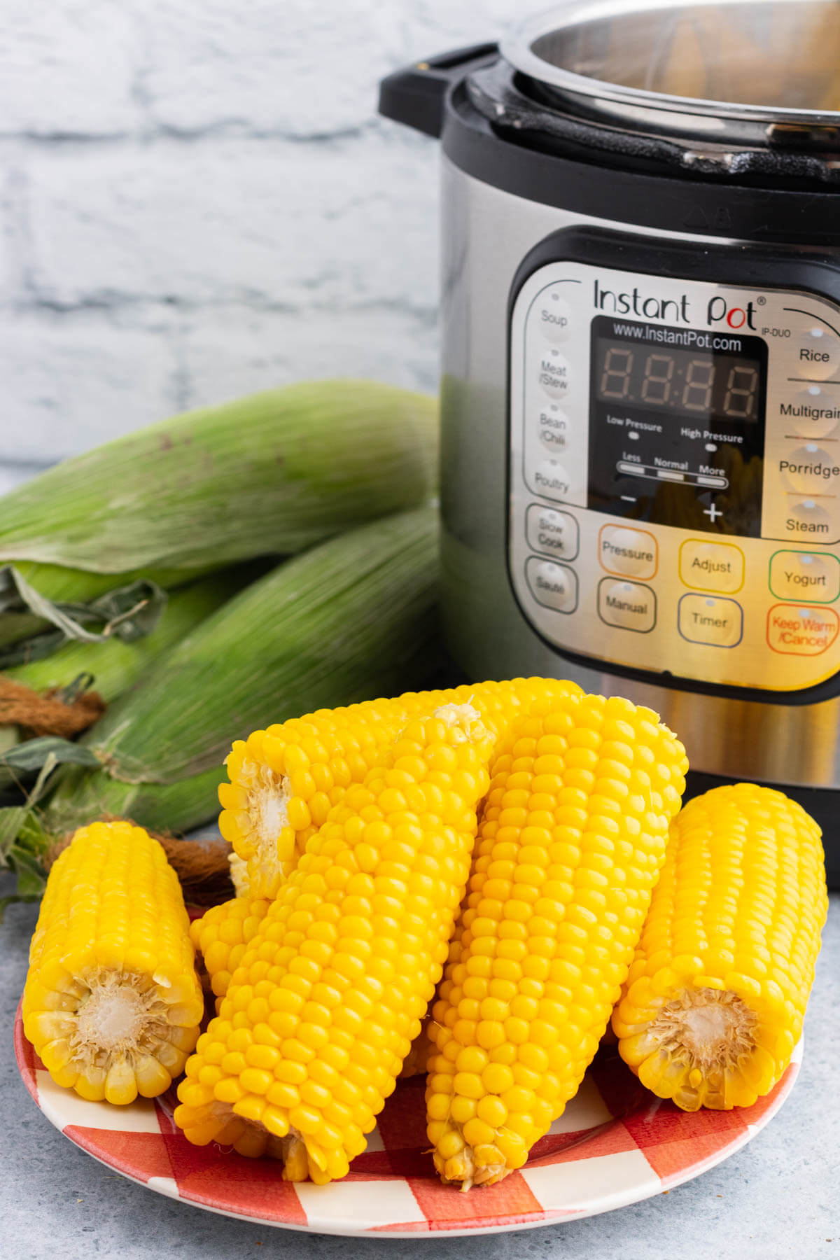 A plate full of golden yellow stack of cooked Instant Pot Corn on the Cob.