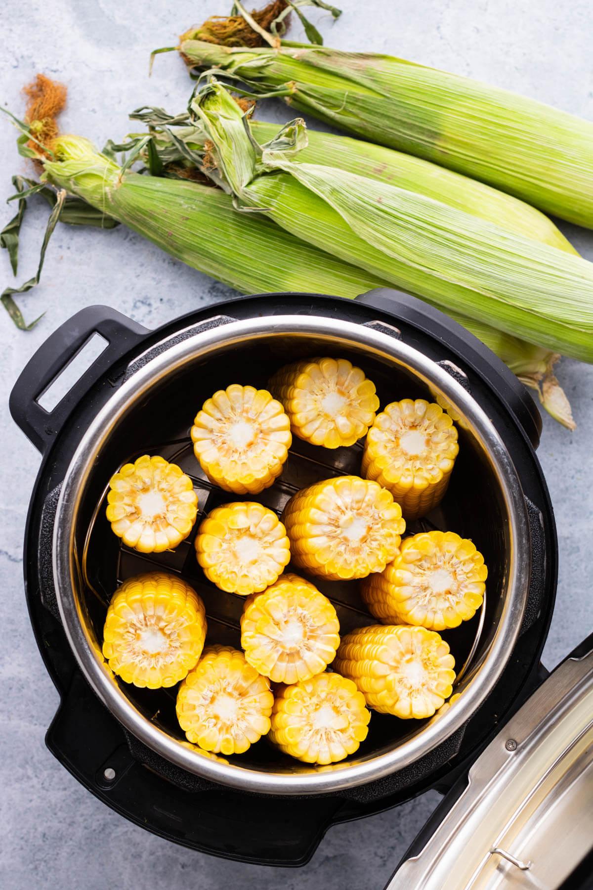 Raw corn arranged inside an Instant Pot.