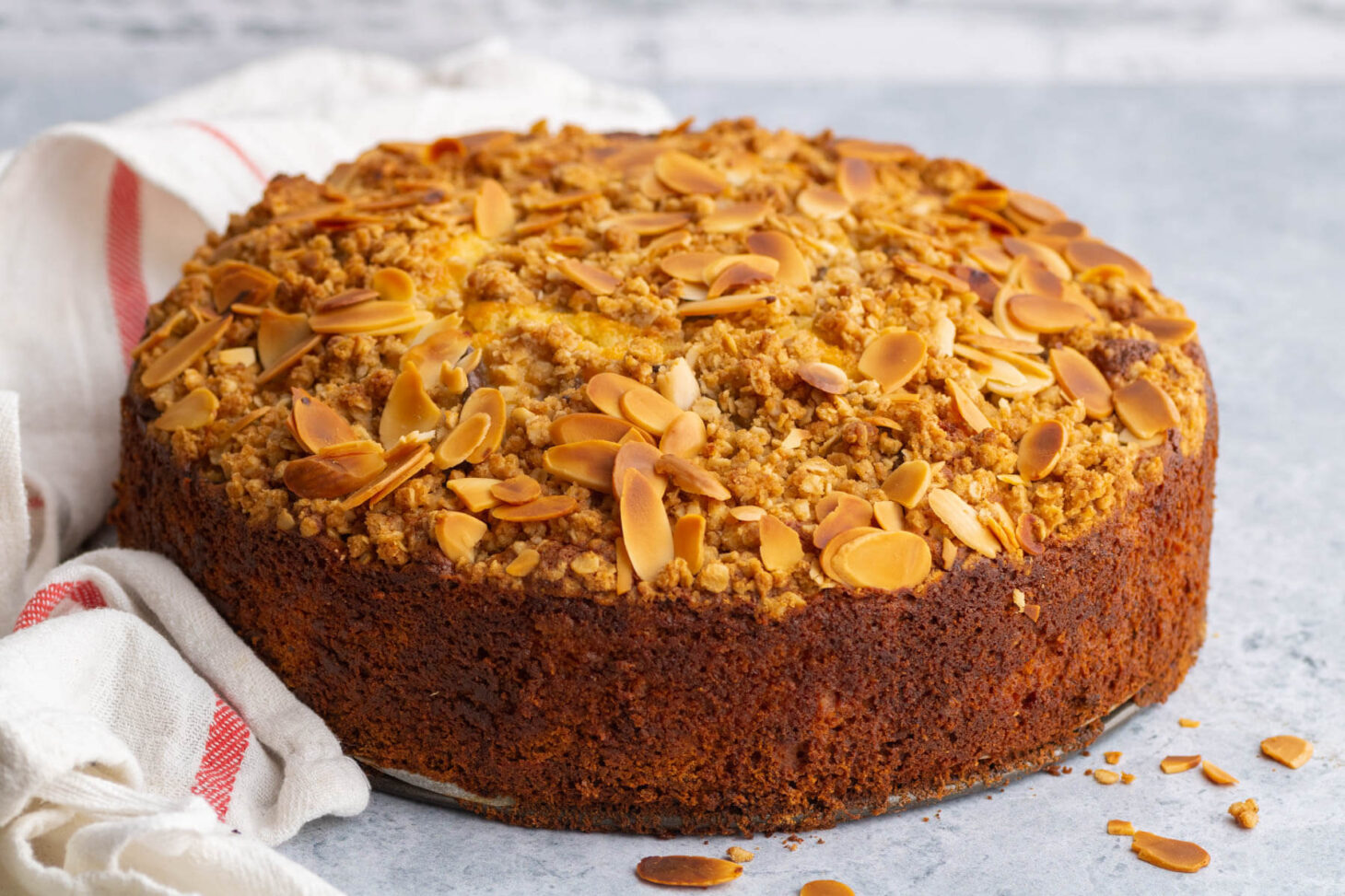 A whole golden baked almond crumble topped Pear Ricotta Cake.