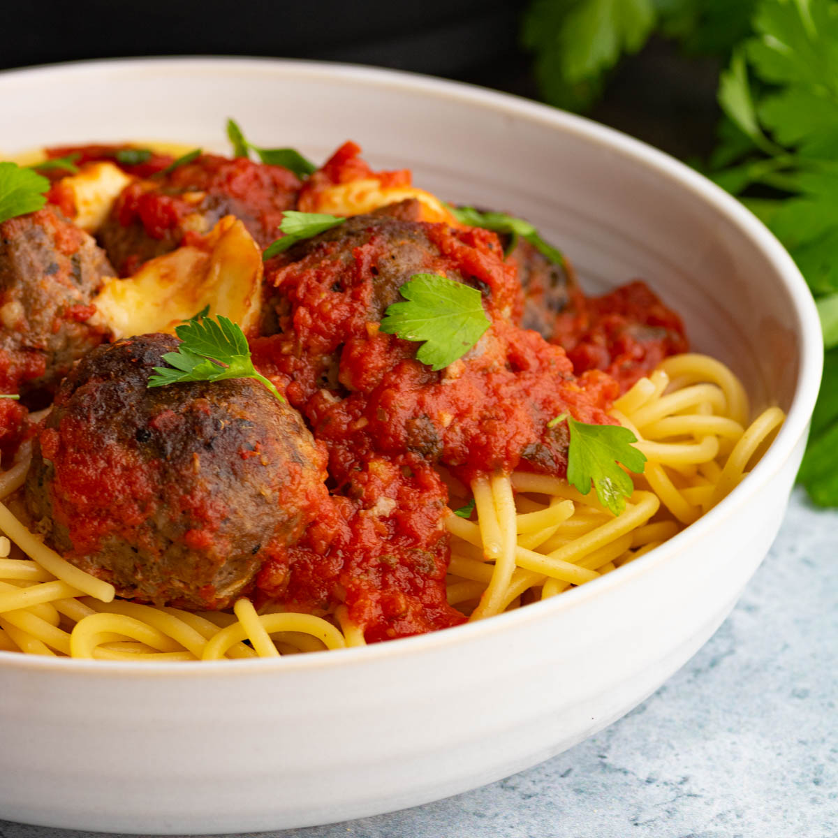 A bowl of spaghetti topped with rich tomato sauce, oven baked meatballs, and Italian parsley to garnish.