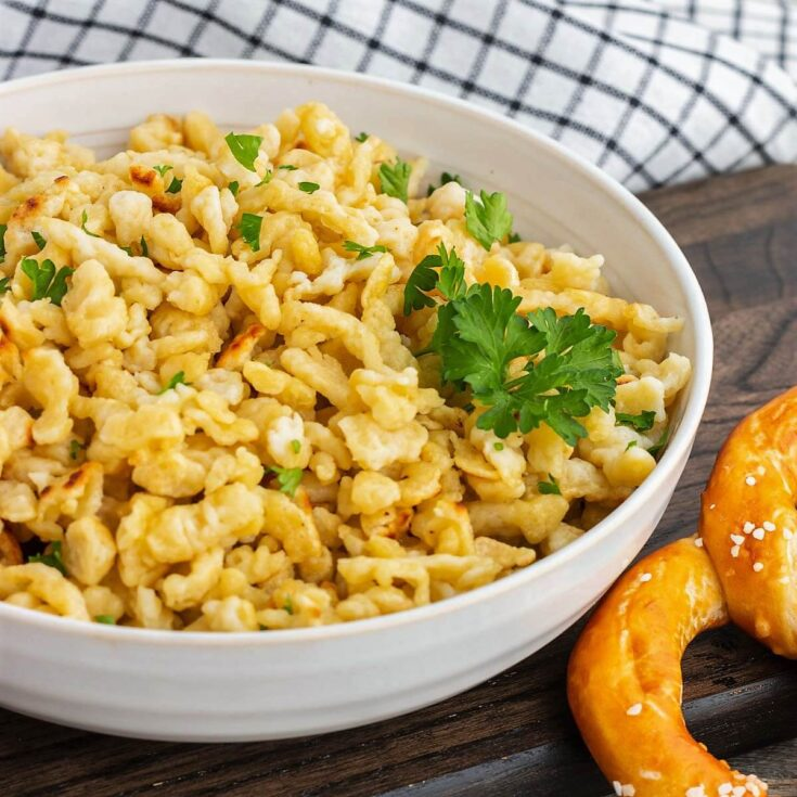 A low white bowl filled with homemade spaetzle noodles garnished with parsley.