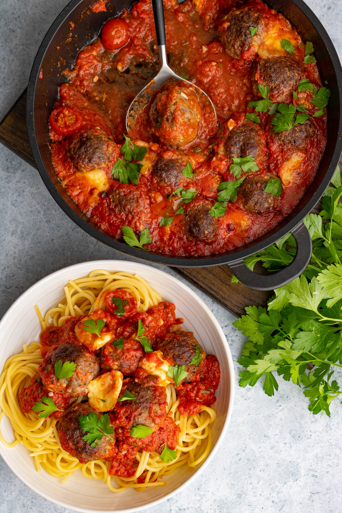 A pan of Oven Baked Meatballs in a rich tomato sauce beside a bowl of spaghetti and meatballs.