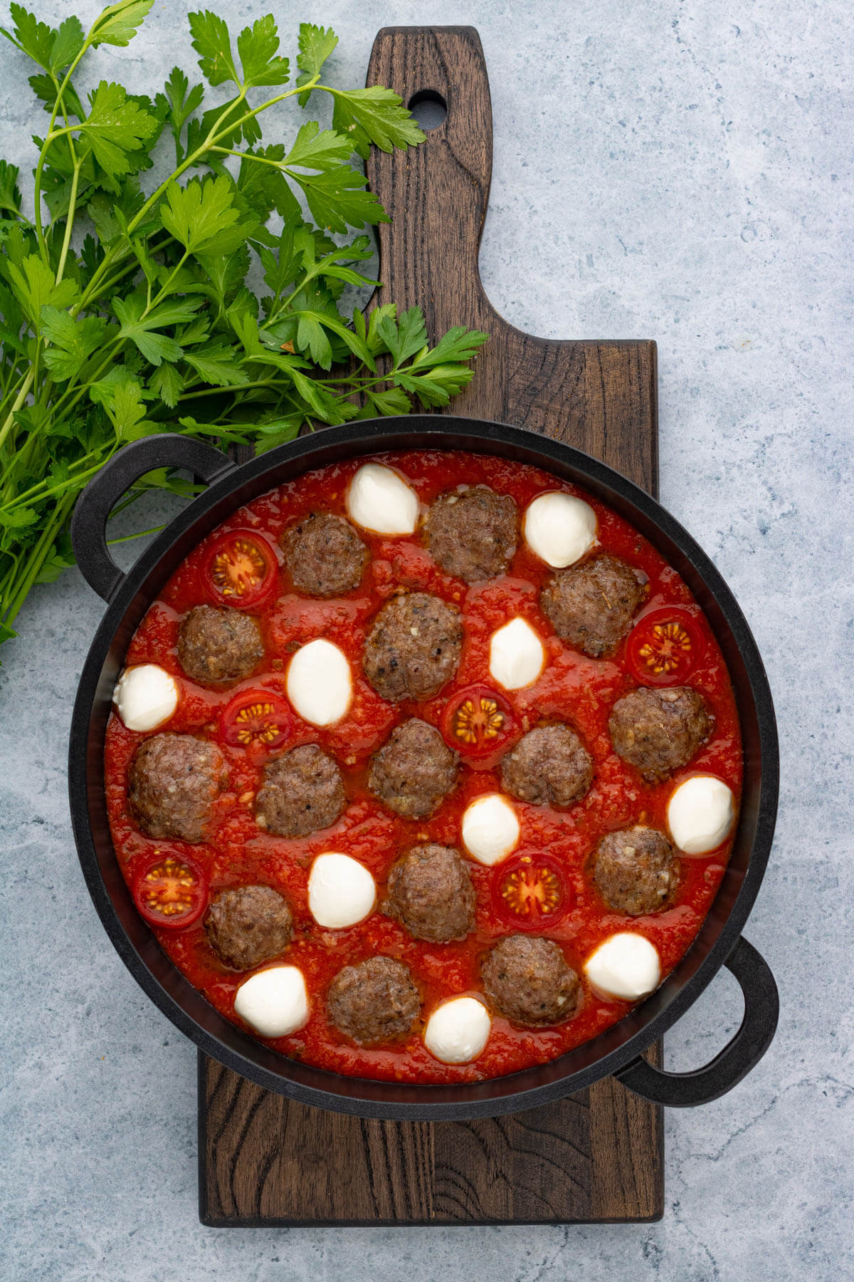A pan of Oven Baked Meatballs in a rich tomato sauce with cherry tomato halves and bocconcini ready to bake in the oven.