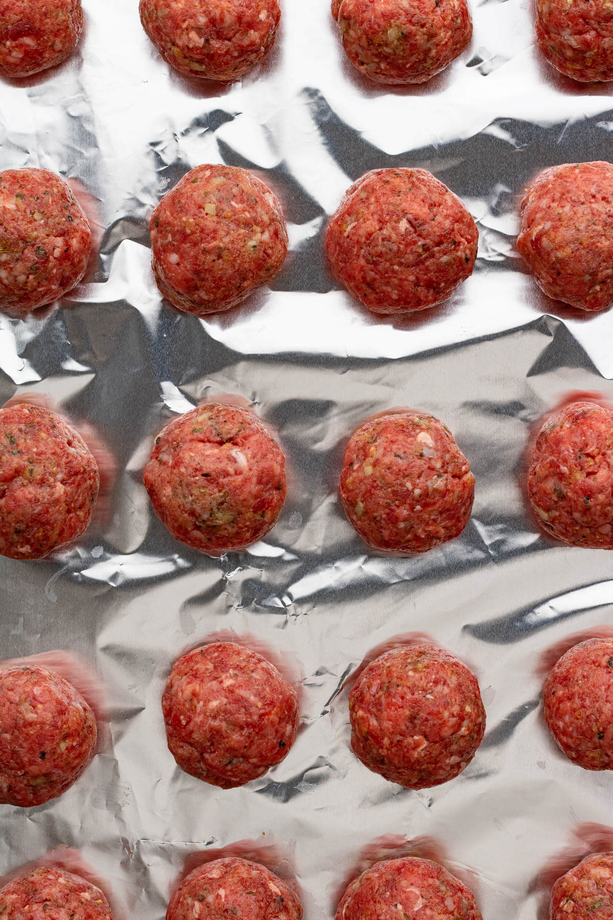 An aluminum foil covered tray of unbaked meatballs.