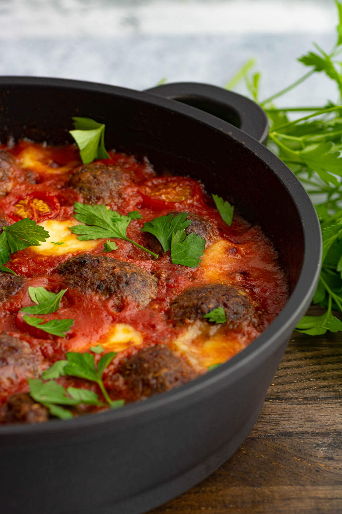 A pan of Oven Baked Meatballs in a rich tomato sauce with melted cheese garnished with Italian parsley.