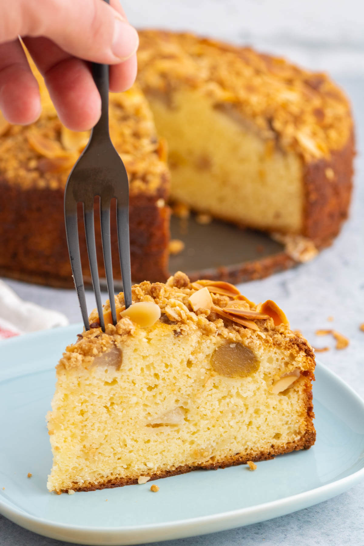 A fork cutting into a slice of Pear Ricotta Cake.