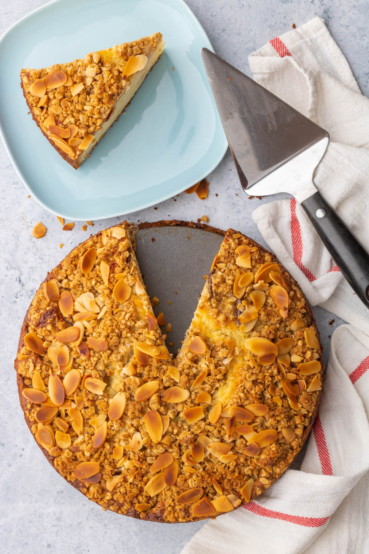 Overhead view of a golden almond crumble topped ricotta cake with a slice taken out.