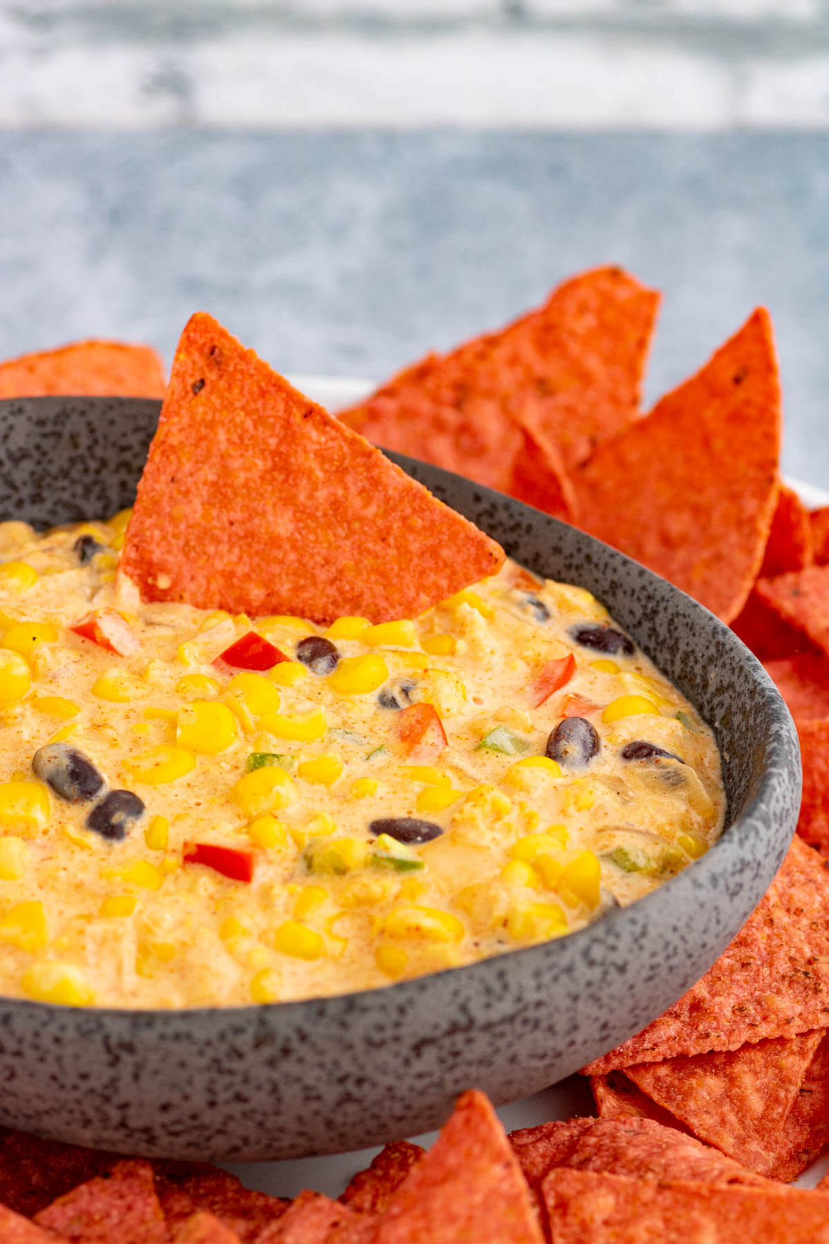 A stone bowl filled with sweet yellow Tex Mex Corn Dip surrounded by red tortilla chips.