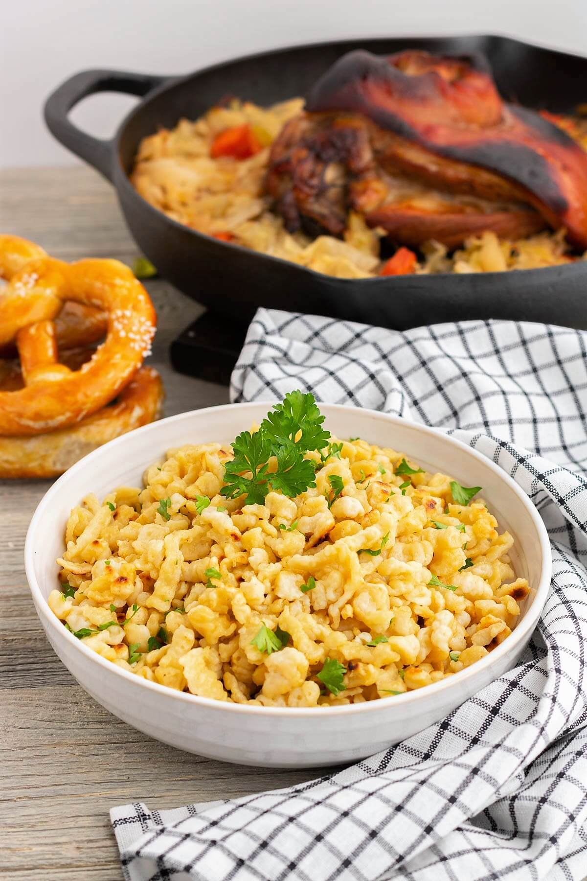A low white bowl filled with homemade spaetzle noodles garnished with parsley in front of a roasted pork knuckle.